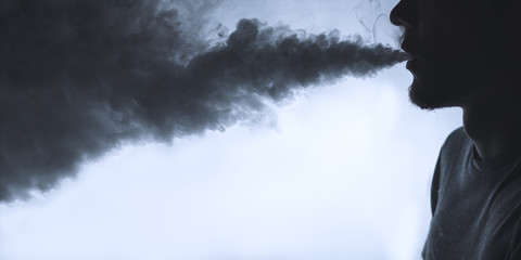 Vaping man. Close-up of a man with a beard releases a cloud of steam