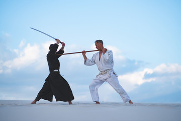 Concentrated men, in Japanese clothes, are practicing martial arts