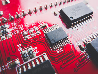 Circuit board in red with electronic components. Electronic circuit board.