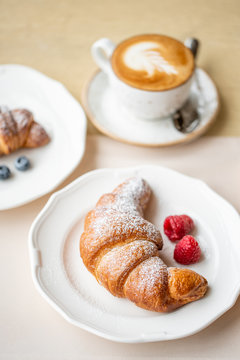 Coffee cappuccino with two croissant on white plate in restaurant. Light morning Breakfast, fresh warm pastries and raspberries
