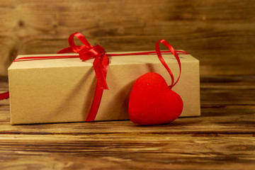Gift box and red heart on wooden background. Valentine's day concept