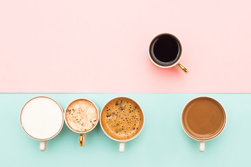 Many cups of coffee on a gently pink and turquoise background. Top view