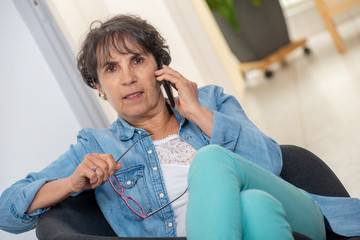 Middle age woman with glasses happy talking using phone