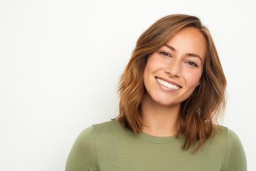 portrait of a young happy woman smiling on white background Wall mural
