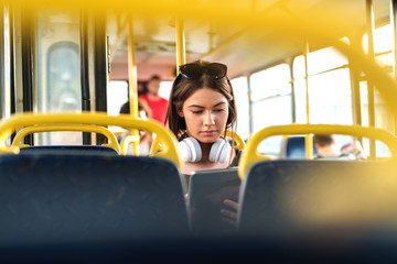 Girl with headphones sitting in a public transportation and watching at tablet.