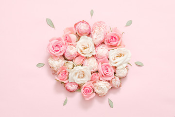 Greeting flower composition. Assorted roses on pink background. Minimal leaves layout.