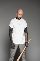 serious tattooed man in white t-shirt holding baseball bat and looking down on grey
