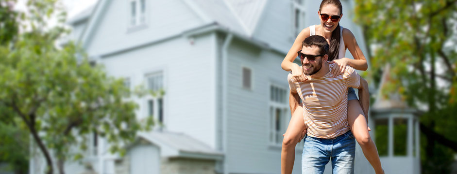 real estate and people concept - happy couple having fun in summer over house background