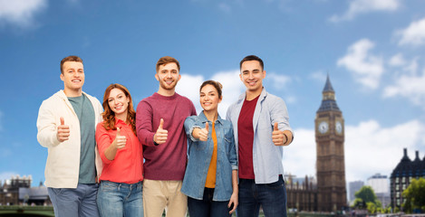 friendship and people concept - group of smiling friends showing thumbs up over london city background
