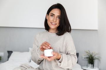 Image of adorable woman 30s holding jar with face cream, in modern bright room