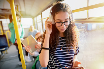 Picture of cute curly girl standing in a public transport and listening to the music.