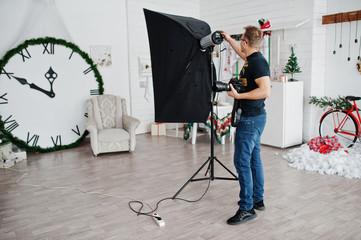 Photographer adjusts the flash light on studio.