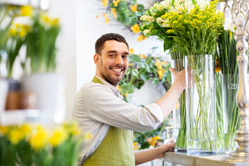 Obraz small business, sale and floristry concept - happy florist man setting flowers at flower shop - fototapety do salonu