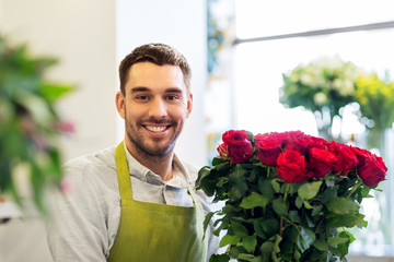 small business, sale and floristry concept - happy smiling florist or seller with bunch of red roses at flower shop