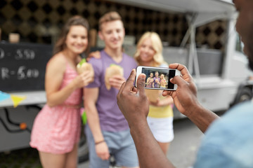 leisure, technology and people concept - young man taking picture of his happy friends eating hamburgers and wok at food truck