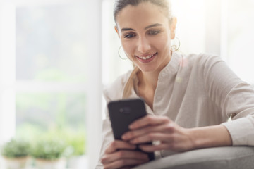Happy woman connecting with her smartphone