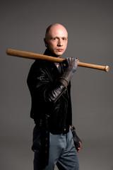 stylish bald man with tattoos holding baseball bat and looking at camera isolated on grey