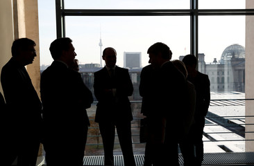 Staff is silhouetted in front of the city skyline ahead the weekly cabinet meeting at the Chancellery in Berlin