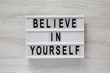 'Believe in yourself' word on modern board on a white wooden surface, top view. From above, flat lay, overhead.