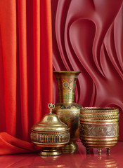 Copperware in oriental style on a red background with theatrical design.
