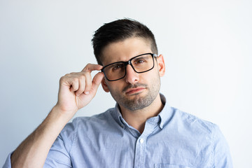 Pensive guy in casual touching temple of eyeglasses. Closeup of young Caucasian man adjusting glasses and staring at camera. Sight concept