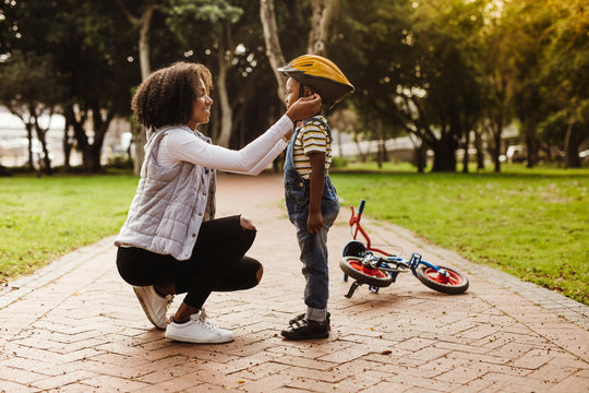 Mother puts her son protective helmet for riding bike