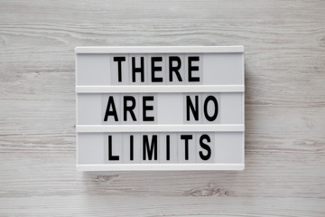 Lightbox with text 'There are no limits' on a white wooden surface, view from above. Flat lay, overhead.