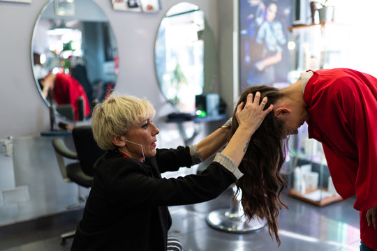 Stylist making hairstyle to young woman