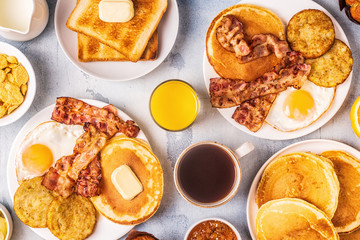 Healthy Full American Breakfast with Eggs Bacon Pancakes and Latkes.