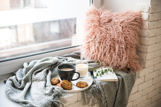 Scandinavian style breakfast, cup of coffee and cookies on cozy windowsill with warm blanket and pillow
