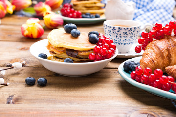 Pancakes with blueberries and currants for breakfast and fresh aromatic coffee. Spring breakfast with flowers on a wooden table. The concept of holidays and Easter.