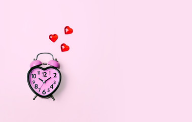 Heart shaped clock on pink background.