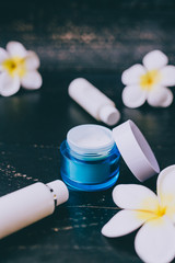 spa skincare products on dark wood background surrounded by tropical flowers