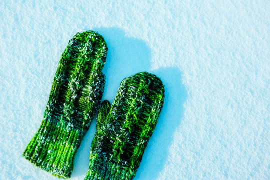 Sunny winter day, snow background surface. A pair of green woolen knitted mittens, warming up concept.
