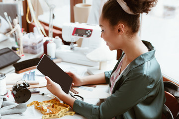 Wall Mural - Close-up of young woman tailor with digital tablet is modeling new clothes