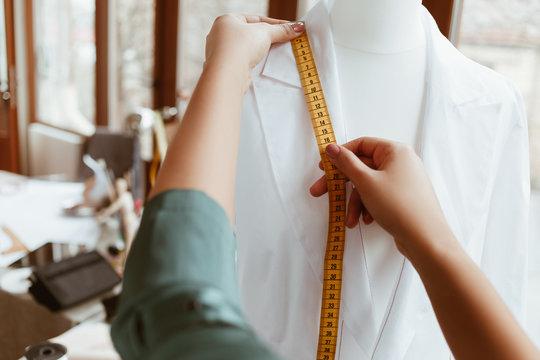 Design studio. Shirt and measurement tape in woman hands
