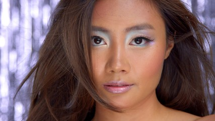 thai asian model in studio with silver rain disco background and party makeup looking straight to the camera