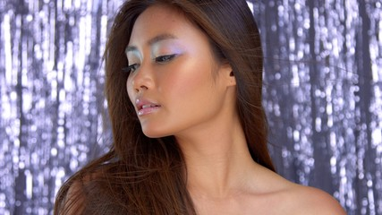 thai asian model in studio with silver rain disco background and party makeup watching aside