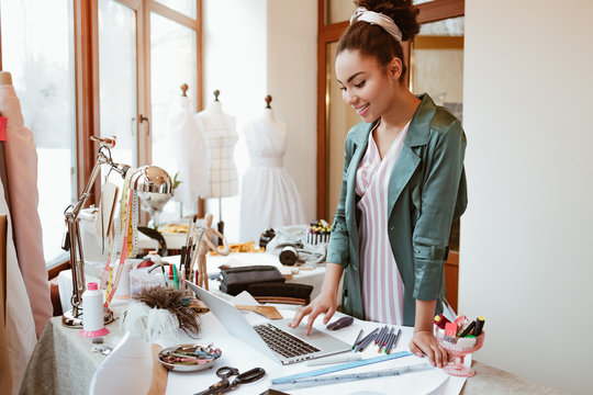 Checking online sales. Young woman tailor with laptop is answering emails