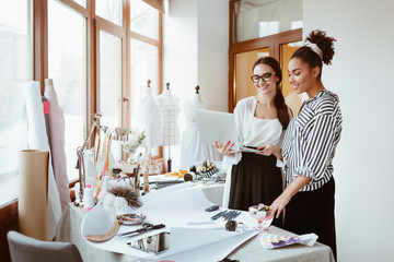 Wall Mural - Project manager consultates young designer. Two women in design studio