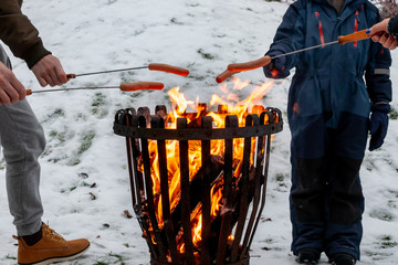 Closeup of family at a campfire grilling hot dog food. Winter snow outdoor scene.