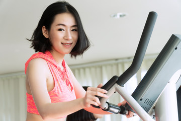 Beautiful woman wearing sportswear cycling exercise in fitness. Sports people running on the treadmill at the gym. Healthy lifestyle and sporting concept.