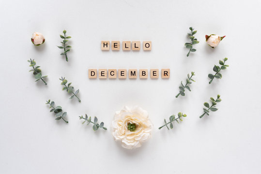 Hello December words on white marble background.