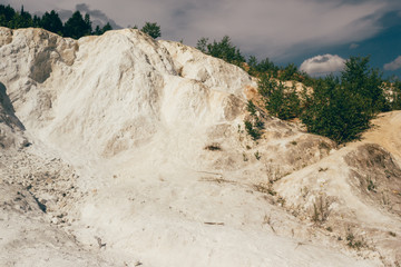 Extraction of talc in career. Abandoned white quarry in forest.
