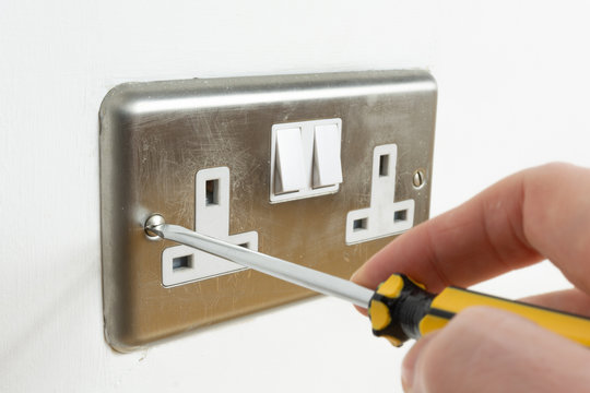 Screwdriver and Stainless steel UK plug socket on white wall