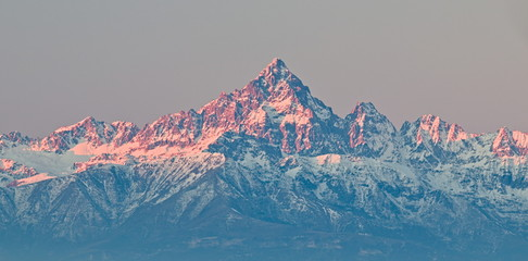 Mount Viso, Alps peak, seen from Superga, Turin, Piedmont, during a winter sunrise with snow and pink light on the glaciers