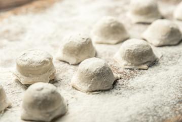 Uzbek national food Chuchvara, like dumplings, on a wooden board, in flour