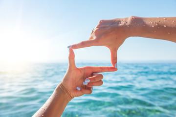 Human hands making frame against sea.