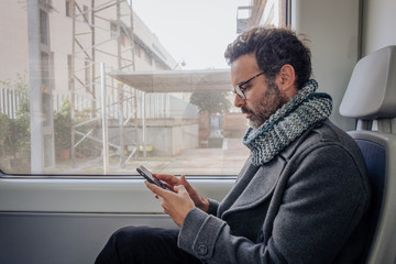 Man in a train looking at the mobile phone