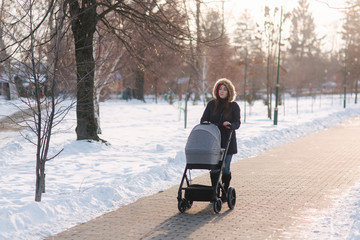 Beautiful mother walking in the park with her little baby in stoller. Woman dressed in blue jaket with hood and jeans. Warm boots